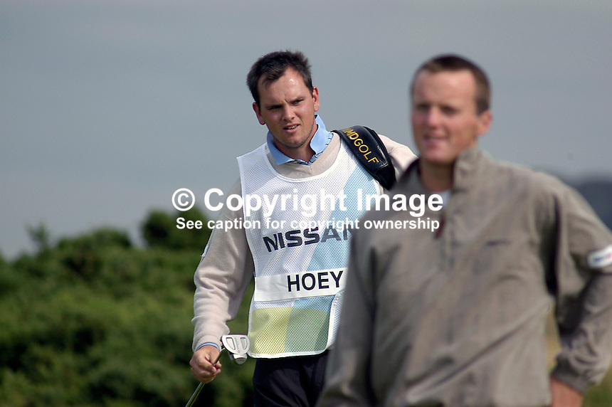 Johnny Foster, golf caddy, from Ballyclare, Co Antrim, N Ireland, pictured with Michael Hoey, professional golfer, N Ireland (out of focus). Taken at Nissan Irish Open, Portmarnock Golf Club, Ireland, in July 2003. Ref: 200307232709...Copyright Image from Victor Patterson, 54 Dorchester Park, Belfast, UK, BT9 6RJ..Tel: +44 28 9066 1296.Mob: +44 7802 353836.Voicemail +44 20 8816 7153.Skype: victorpattersonbelfast.Email: victorpatterson@mac.com.Email: victorpatterson@ireland.com (back-up)..IMPORTANT: If you wish to use this image or any other of my images please go to www.victorpatterson.com and click on the Terms & Conditions. Then contact me by email or phone with the reference number(s) of the image(s) concerned.