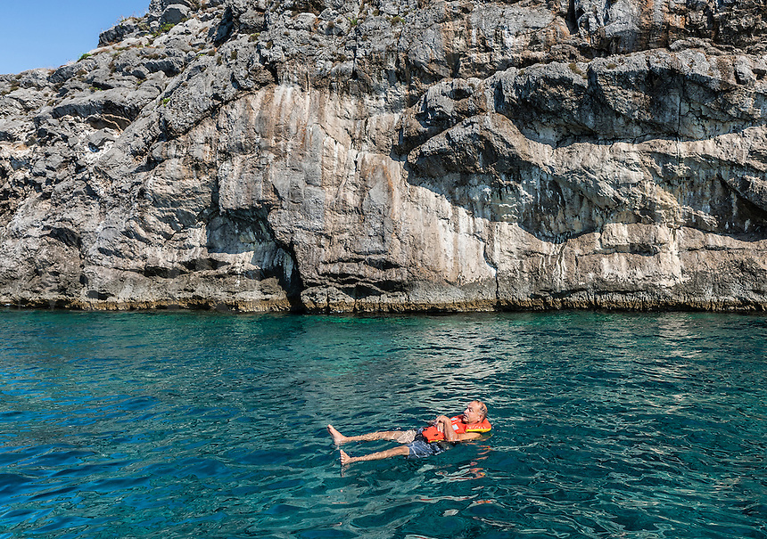 Man enjoys the aquamarine waters off the island of Capri, Naples, Italy