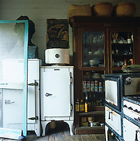 A large glass-fronted cupboard and a 1930's cooker and fridge furnish this makeshift kitchen
