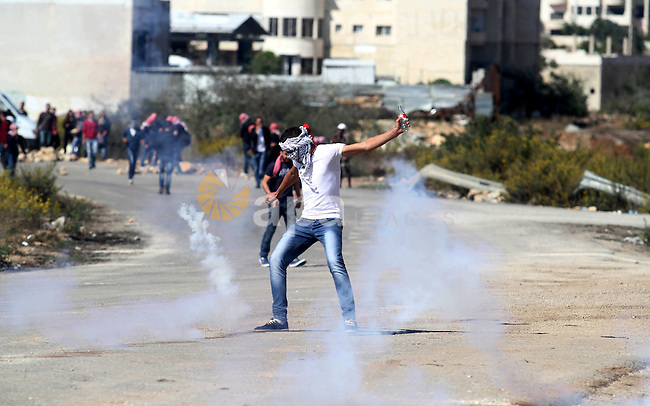 Palestinian protesters throw stones towards Israeli security forces during clashes at a protest to show solidarity with al-Aqsa mosque, outside Israel's Ofer military prison near the West Bank city of Ramallah October 21, 2014. A Palestinian official on Monday called for holding an emergency Arab and Islamic summit to discuss Israeli plans to divide the Al-Aqsa Mosque compound between Jews and Muslims. In recent months, groups of Jewish settlers accompanied by Israeli security forces have repeatedly forced their way into East Jerusalem's flashpoint Al-Aqsa Mosque complex. Photo by Shadi Hatem