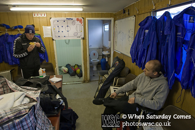 Glossop North End 0 Barnoldswick Town 1, 19/02/2011. Surrey Street, North West Counties League Premier Division. Glossop North End manager Steve Young eating a pre-match snack while chatting to defender Danny Broome in the home dressing room at the club's Surrey Street ground before their game with Barnoldswick Town in the Vodkat North West Counties League premier division. The visitors won the match by one goal to nil watched by a crowd of 203 spectators. Glossop North End celebrated their 125th anniversary in 2011 and were once members of the Football League in England, spending one season in the top division in 1899-00. Photo by Colin McPherson.