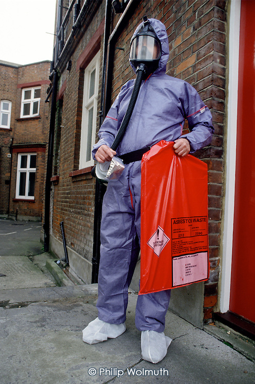 A local authority Environmental Health Officer wearing protective clothing carries asbestos waste from a building in Haringey, North London.