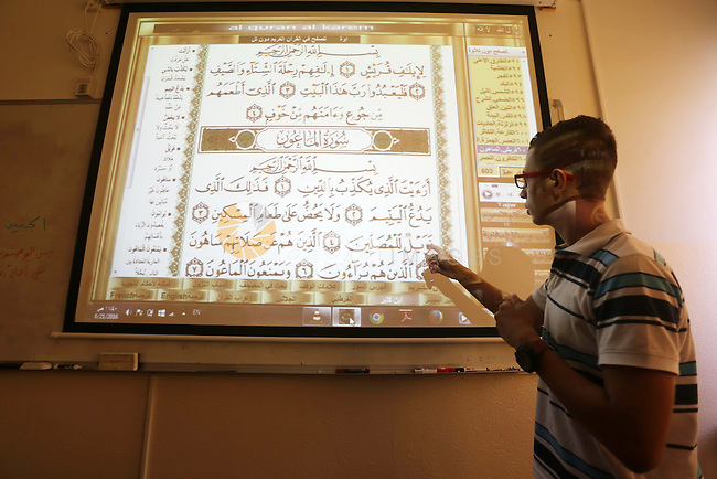 A Palestinian young man uses sign-language to read a projection of the Koran, Islam's holy book, during a class for deaf students at a religion school in Gaza City on June 21, 2016 during the Muslim fasting month of Ramadan. Photo by Mohammed Asad