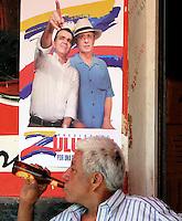 VILLETA - COLOMBIA. 17-05-2014.  Un hombre sin identificar bebe cerveza frente a un cartel de Oscar Ivan Zuluaga candidato presidencial en Colombia por el partido Centro democrático quien visita Villeta, Colombia, hoy 18 de mayo de 2014 previo a las elecciones presidenciales el próximo 25 de mayo de 2014./ An unidentified man drinks a beer in front of poster of Oscar Ivan Zuluaga presidential colombian canditate by Democratic Center party who visit Villeta, Colombia, today May 18 2014 prior the Presidential elections in May 25 2014. Photo: VizzorImage / Nestor Silva / Cont