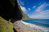 Man walking beneath high cliffs near rocks and the ocean off of Moloka'i's north shoreline, with Kalaupapa Peninsula in the distance