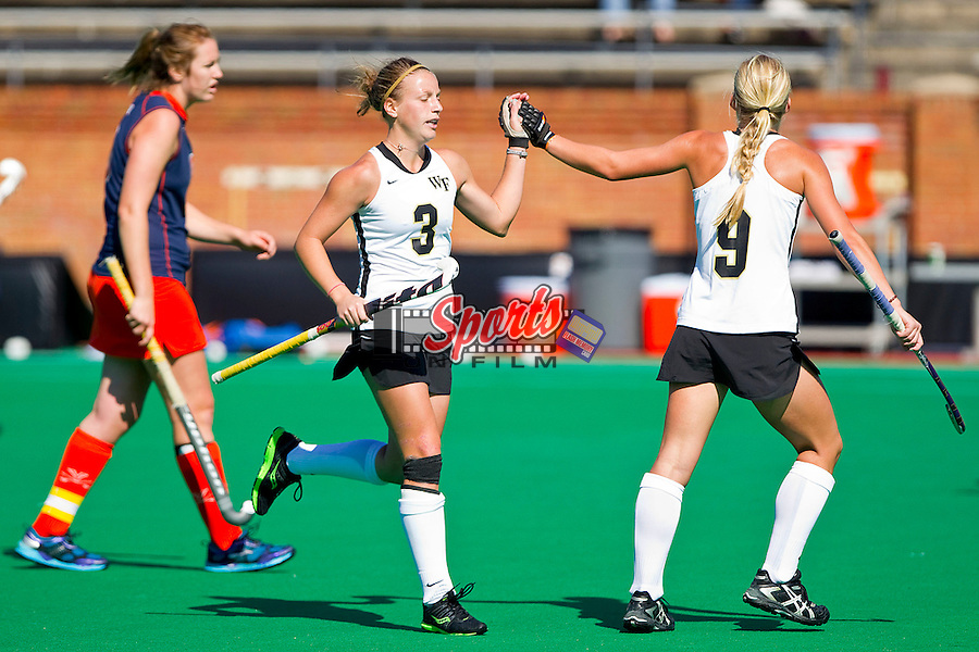 Emily Cummings #3 of the Wake Forest Demon Deacons gets a high five from teammate Molly Murphy #9 after scoring a goal against the Virginia Cavaliers at Kentner Stadium October 22, 2011, in Winston-Salem, North Carolina.  The Demon Deacons defeated the Cavaliers 5-0..  Photo by Brian Westerholt / Sports On Film