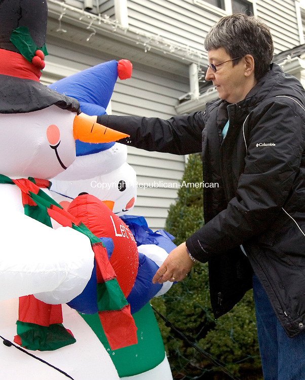 BEACON FALLS, CT. 07 December 2010-121310SV02--Rosalie Stronkowski of Beacon Falls shakes the rainwater out of her Christmas snowmen on her front lawn in Beacon Falls Monday. The recent rain took its toll on the lawn ornaments weighing them down.<br /> Steven Valenti Republican-American