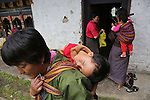 Woman and child. A traditional Puja celebration, a yearly Buddhist festival by the local community, Chuchizshey temple, Bumthang, Bhutan..Bhutan the country that prides itself on the development of 'Gross National Happiness' rather than GNP. This attitude pervades education, government, proclamations by royalty and politicians alike, and in the daily life of Bhutanese people. Strong adherence and respect for a royal family and Buddhism, mean the people generally follow what they are told and taught. There are of course contradictions between the modern and tradional world more often seen in urban rather than rural contexts. Phallic images of huge penises adorn the traditional homes, surrounded by animal spirits; Gross National Penis. Slow development, and fending off the modern world, television only introduced ten years ago, the lack of intrusive tourism, as tourists need to pay a daily minimum entry of $250, ecotourism for the rich, leaves a relatively unworldly populace, but with very high literacy, good health service and payments to peasants to not kill wild animals, or misuse forest, enables sustainable development and protects the country's natural heritage. Whilst various hydro-electric schemes, cash crops including apples, pull in import revenue, and Bhutan is helped with aid from the international community. Its population is only a meagre 700,000. Indian and Nepalese workers carry out the menial road and construction work.