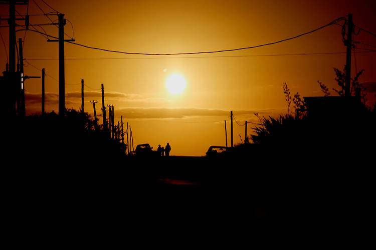 Silhouetted couple walks down the street into the setting sun.