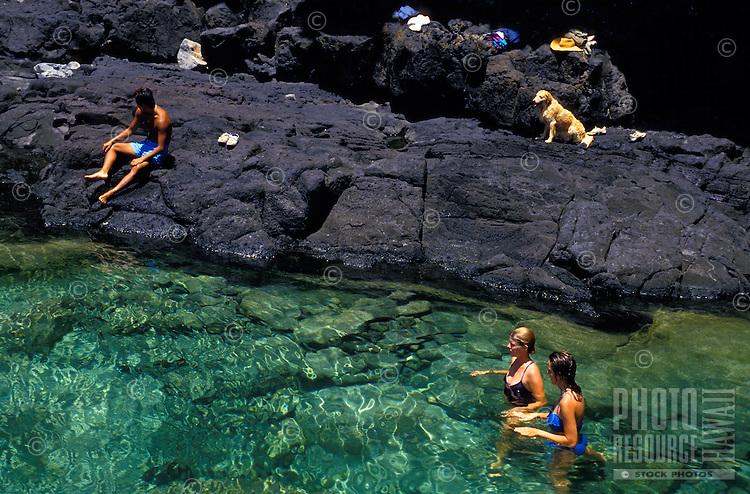 People and a dog enjoying a tide pool located along the coastal hike to Makapuu Point, east Oahu