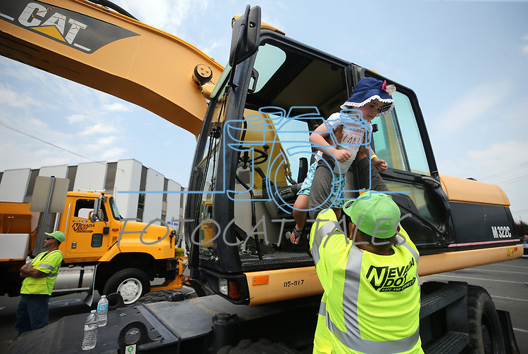 Craig Santos, with NDOT, helps Stella DeBoor, 3, out of a piece of heavy equipment at the Touch-a-Truck event at the Carson City Library in Carson City, Nev., on Saturday, Aug. 5, 2017. <br /> Photo by Cathleen Allison/Nevada Photo Source