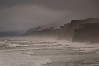 Fog and mist shroud the bluffs standing above the incoming surf at Pescadero State Beach on the California coast south of San Francisco.