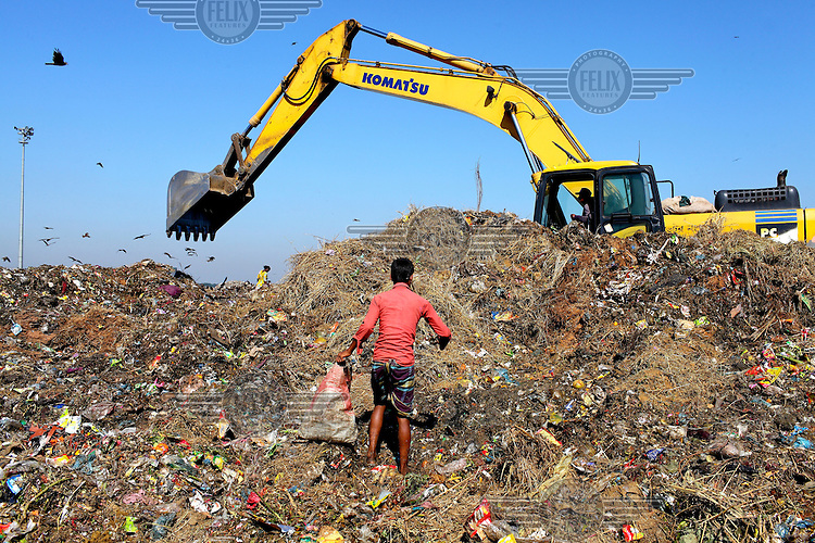 A young man looks for recyclable material at the biggest rubbish dump in Dhaka. The city alone generates about 3500 to 4000 metric tons of solid waste each day.