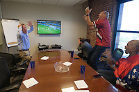 San Francisco, CA - Tuesday, July 1, 2014: In the second half, several employees at Arthur J. Gallagher insurance company took over a small meeting room to watch the game. They reacted when the USA just missed a goal moments before the end of regulation. Workers watched the  USA vs. Belgium World Cup Round of 16 game in San Francisco.
