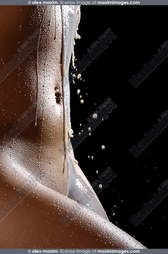 Closeup of a naked woman body with splashes of milk on it