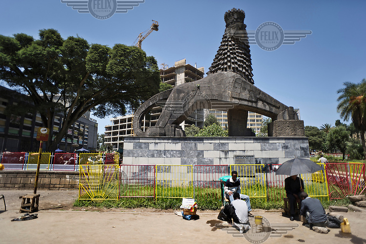 People have their shoes polished in front of a statue of an Abyssinian lion in Addis Ababa.