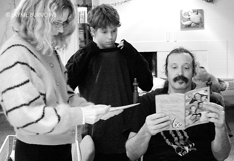 Erika Reaper (left), 12-year-old Jason Reaper (center), and Michael ?Reaps? Reaper openly discuss the family?s untraditional lifestyle.  Reaps is seen here reading a brochure about an upcoming retreat for couples looking to have sexual connections with other couples while Jason looks on at their family home in Isla Vista, Calif. on Tuesday, February 22, 2005.  The Reapers are a polyamorous couple, which means that they participate in romantic relationships with other people.  What began as a sexual exploration with new partners turned to something more significant when Erika fell in love with Russell Williams last year, and she is now in a committed relationship with both her husband and Williams.  Since Erika's unexpected relationship with Williams has occurred, Reaps is now able to date other people outside of their marriage and jealousy often rears its head.  (Photo by: Jayme Burrows/Brooks Institute) Polyamory: the act of having more than one romantic love at a time.  This is a photo essay on a couple who are involved in a polyamorous lifestyle where both of the married partners have loving, committed relationships outside of the marriage.