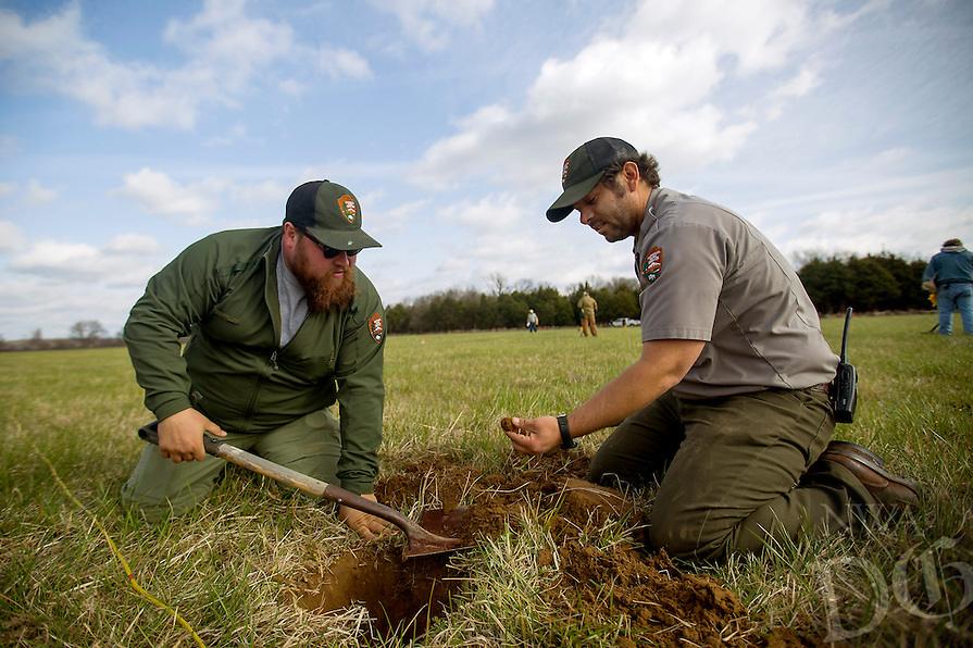 NWA Democrat-Gazette/JASON IVESTER<br /> Alex Swift (left), interpreter, and Nolan Moore, biologist, unearth a 12-pound canister on Wednesday, March 23, 2016, in Ruddick's Field at the Pea Ridge National Military Park. Archaeologists and volunteers are digging at the field throughout the week searching for fragments from the Civil War battle site.