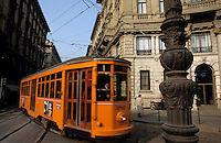 Commuters travelling on the tram moving through a street in Corso Magenta, Milan, Italy.