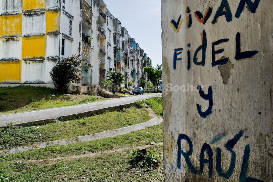 A painted writing, supporting the regime of Fidel Castro and his brother Raul Castro, seen on the wall of a concrete apartment block in the neighbourhood of Abel Santamaría, a public housing complex in Santiago de Cuba, Cuba, 31 July 2008. About 50 years after the national rebellion, led by Fidel Castro, and adopting the communist ideology shortly after the victory, the Caribbean island of Cuba is the only country in Americas having the communist political system. Although the Cuban state-controlled economy has never been developed enough to allow Cubans living in social conditions similar to the US or to Europe, mostly middle-age and older Cubans still support the Castro Brothers' regime and the idea of the Cuban Revolution. Since the 1990s Cuba struggles with chronic economic crisis and mainly young Cubans call for the economic changes.