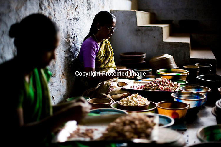 Women are seen shelling raw cashews in cashew processing factories in Prassala, Kanyakumari district in Tamil Nadu, India.. .An estimated number of 500,000 women process cashews for a living in Tamil Nadu and Kerela. 2 million people are employed by cashew industry across India making it the world's biggest exporter of shelled cashews. .The working conditions in these processing units are way below industry standards and violates the basic rights. Wages are as low as Rs. 50 (US $1) per day. The problems for these women is not restricted to low wages. Many women are being injured by their jobs as the factory owners cut corners with health and safety. Oil released during the cashew shelling process is highly caustic, leading to common cases of dermatitis, blistering and discolouration of workers' skin. Women working in these units suffer from pains in their leg muscles, backs and knee joints after squatting positions on mud or concrete floors. It is very rare to find tables and chairs provided on shelling duty..Cashew workers' main concern is to increase their earnings and provide better working conditions. .Photo: Sanjit Das