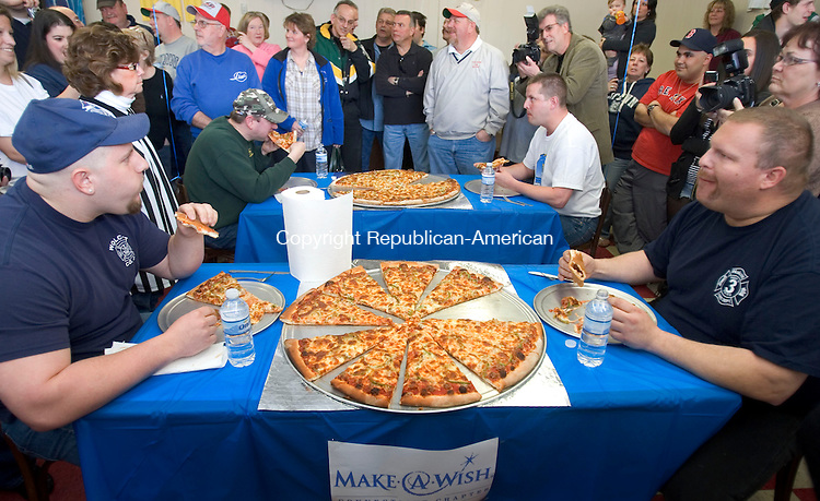 WOLCOTT, CT. 31 March 2011-040211SV07--Sitting, from left, Firefighter Larry Rossi Jr., Police Sgt. Pat Malloy, Officer Chris Charette, and Fire Lieutenant John Dalnegro as they compete in a police vs. firefighters, 10 pound pizza eating contest. The event was held at Five Guys Flippin' Pies in Wolcott Saturday. The firefighters won eating 7.5 pounds while the police officers ate 7.1 pounds of pizza. The event was sponsored by Miss Wolcott Outstanding Teen Taylor Way. Ten percent of sales on Saturday benefited her platform, the Make-a-Wish Foundation.<br /> Steven Valenti Republican-American