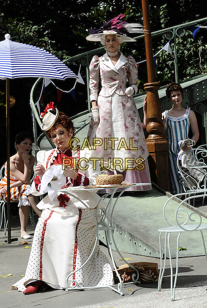 "MILLICENT MARTIN & LINDA THORSON.The ""Gigi"" photocall, Open Air Theatre, Regent's Park, London, England..August 12th, 2008.stage acting dress-up costume white red polka dot dress hat full length sitting needlepoint floral print .CAP/CAN.©Can Nguyen/Capital Pictures."