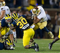 Irish running back Amir Carlisle (3) bounces off Michigan Wolverines safety Thomas Gordon (30) in the second quarter.