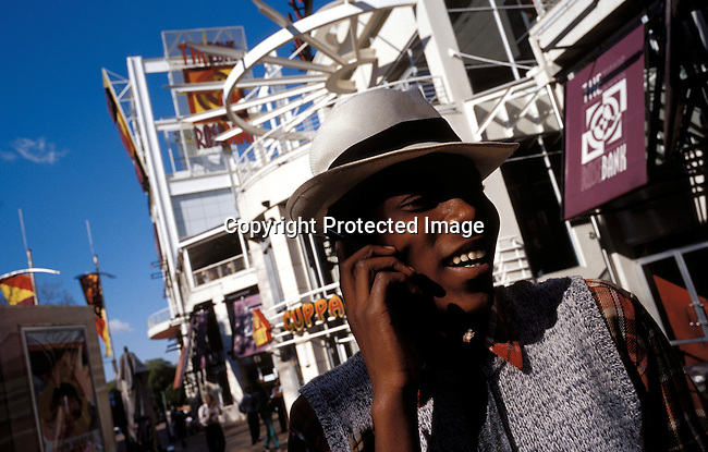 JOHANNESBURG, SOUTH AFRICA - MAY 28: An unidentified young man talking on his mobile phone on May 28, 2002 at The Zone, a trendy shopping mall and gathering point for youth in Rosebank a suburb in Johannesburg, South Africa. He comes here on the weekends to hang out with other youth, black and white, and to check out the latest fashion clubs etc. After eight years into democracy a new black middleclass and elite is growing, and they have money to spend on houses, cars and entertainment. .(Photo: Per-Anders Pettersson/ iAfrika Photos...