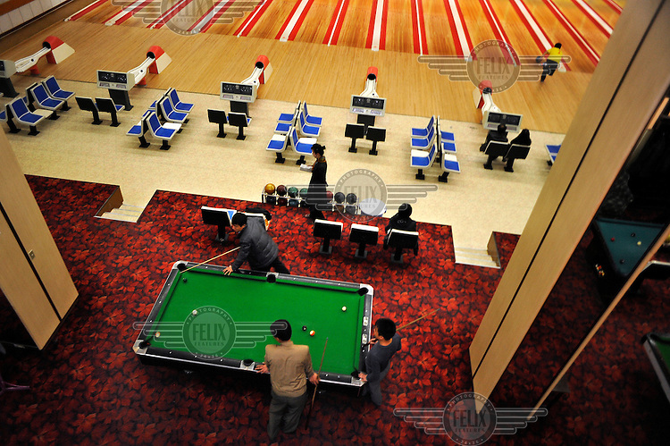 A group of men play a  game of pool on a table in  acity centre bowling alley.