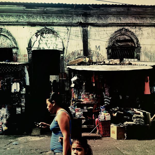 A Salvadorean woman, holding her daughter, walks along the street market vendors in the center of San Salvador, El Salvador, 21 December 2013.