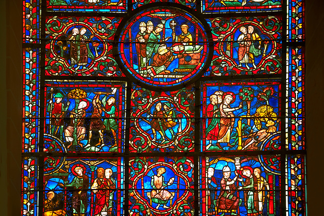 Medieval Windows of the Gothic Cathedral of Chartres, France, dedicated to St Martin of Tour.    A UNESCO World Heritage Site. In the top central oval panel St Martin is ordained Bishop of Tour, box below left Martin is attacked by brigands.