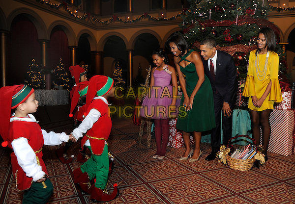 "United States President Barack Obama, first lady Michelle Obama (2nd,L) and daughters Malia (R) and Sasha greet children dressed as elves prior to attending performances at the annual ""Christmas in Washington"" gala, Washington, DC., USA..December 11th, 2011.full length family kids children married husband wife purple green yellow dress black suit elf elves bending leaning .CAP/ADM/MT.©Mike Theiler/Pool/CNP/AdMedia/Capital Pictures."