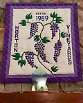A hand-sewn quilt commemorating Horton Vineyards' founding in 1989 is displayed with an award over the fireplace in the winery's tasting room.