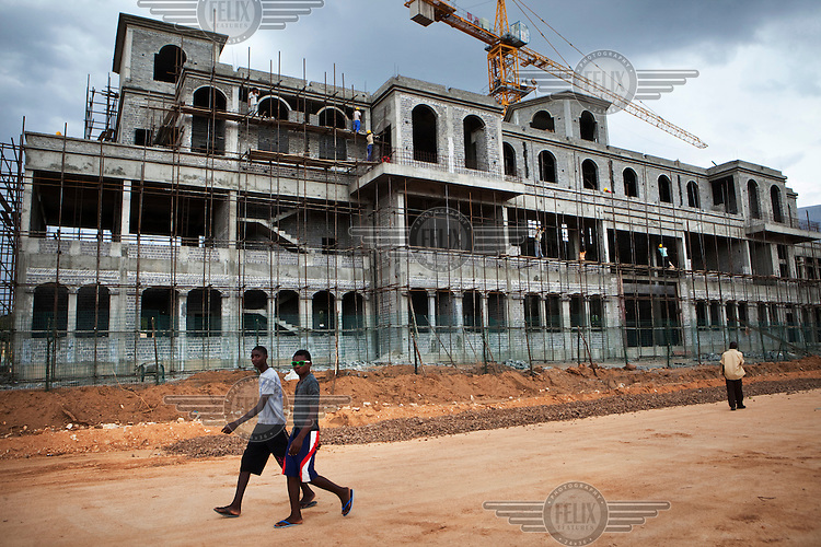 Boys walk past a station and railway building under construction by Chinese workers, part of a development aid project by China in Angola in exchange for petroleum.
