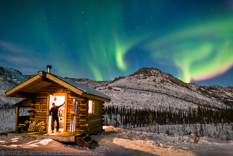 Man in cabin doorway watches aurora for Alaska cottage