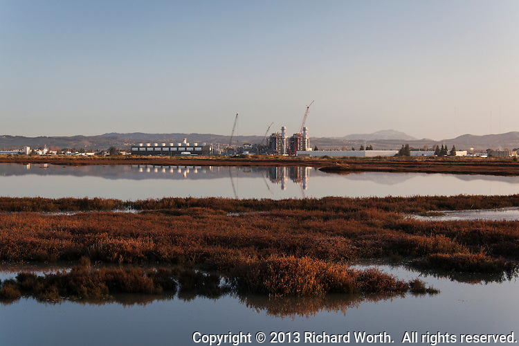 The Russell City Energy Center is a natural gas-fired power plant under construction, and nearing completion, along San Francisco Bay.  Here, at sunrise, it is reflected in ponds of the Hayward Regional Shoreline wetlands. an element of the San Francisco Bay Estuary, added to the Ramsar Convention on World Wetlands Day, Feb. 2, 2013.  For more, see:  http://www.ramsar.org/cda/en/ramsar-news-archives-2013-usa-35/main/ramsar/1-26-45-590%5E26050_4000_0__