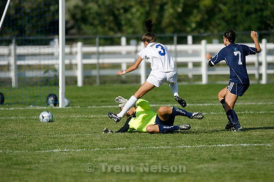 South Jordan - Bingham's Liz Christensen leaps over and scores on Juan Diego goalkeeper Allison Bruder to tie the game 3-3. Bingham vs. Juan Diego girls high school soccer Tuesday, August 25 2009. 3A Juan Diego managed to tie 5A Bingham 3-3..