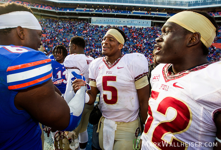 FSU quarterback Jameis Winston (5) and linebacker Ukeme Eligwe (52) greet Gator defensive lineman Dante Fowler, Jr. after the #2 ranked Florida State Seminoles 37-7 victory over the Florida Gators at Ben Hill Griffin Stadium in Gainesville, Florida November 30, 2013.  Florida State had an undefeated regular season at 12-0.