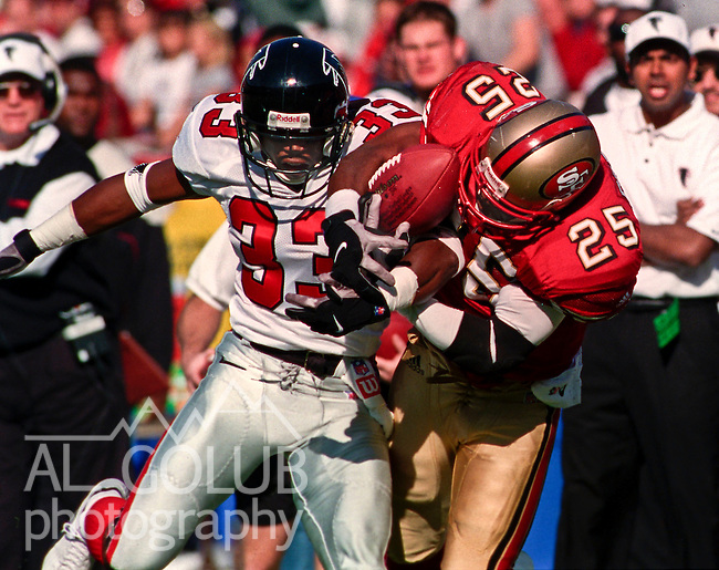 San Francisco 49ers vs. Atlanta Falcons at Candlestick Park Sunday, November 19, 2000.  49ers beat Falcons 16-6.  Atlanta Falcons defensive back Ashley Ambrose (33) attempt to rip ball from San Francisco 49ers running back Charlie Garner (25).