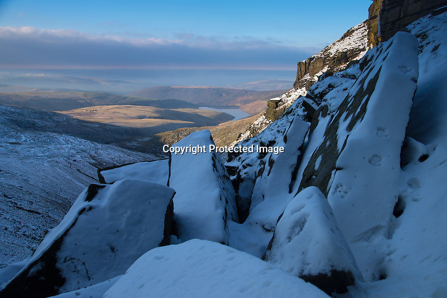 """20/01/16<br /> <br /> <br /> The view looking west over Kinder reservoir and towards Cheshire and Wales.<br /> <br /> Only 160 miles, as the crow flies from central London, Will Flanagan (36), explores the stunning icicles at Kinder Downfall near Hayfield in the Derbyshire Peak district today. After days of cold sub-zero temperatures the 100 ft waterfall finally froze over last night.<br /> <br /> Will said: """"I had to set off at dawn to to get up here. I've been watching the overnight temperatures and thought there's be a chance it would be frozen today. <br /> <br /> """"As the sun began to rise the ice started to melt. I could here it cracking beneath my feet and I saw a few giant icicles crash down. So I didn't stay up there very long!<br /> <br /> """"I definitely wouldn't have wanted to climb any higher up it today even if I'd had ropes with me - the ice wouldn't have been strong enough to support me. If I'd have arrived any later I wouldn't have risked going all the way up. <br /> <br /> """"But all the same it was an awesome spectacle and one of the most extreme walks I've ever done.""""<br /> <br /> The waterfall flows from Kinder Scout the only mountain in the Derbyshire Peak District between Hayfield and Edale. <br /> <br /> All Rights Reserved: F Stop Press Ltd. +44(0)1335 418365   www.fstoppress.com."""
