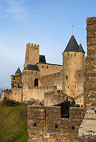 Low angle view of Comtal Castle with the square Pinte Tower on the left, the Justice Tower on the right, seen from the Aude Gate, Citadel of Carcassonne, Aude, France, pictured on February 24, 2007, in the afternoon. The two outer walls of the concentric fortified city are defended by towers and barbicans, and a draw bridge across a moat leads to the keep of the castle. Carcassonne was a stronghold of Occitan Cathars during the Albigensian Crusades but was captured by Simon de Montfort in 1209. He added extra fortifications and Carcassonne became a citadel on the French border with Aragon. The fortress restored in 1853 by Eugene Viollet-le-Duc. Today it is a UNESCO World Heritage site. Picture by Manuel Cohen.