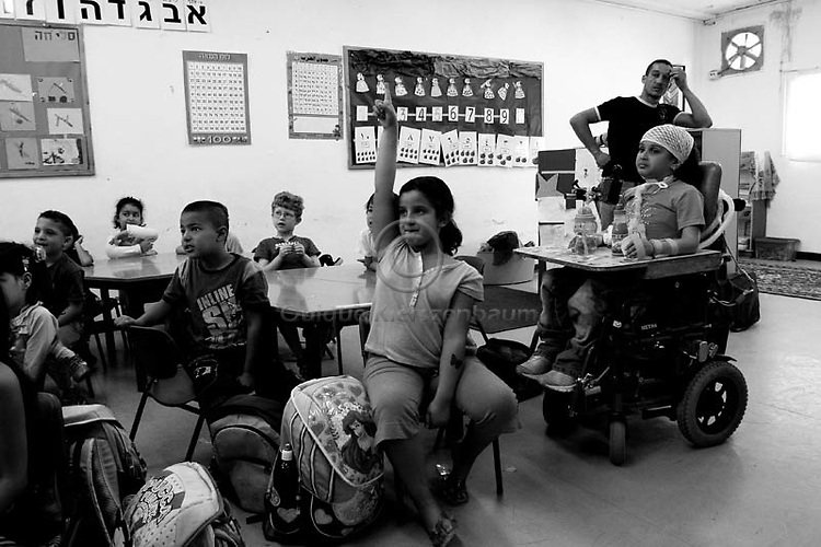 Maria Amin(R), 6 is seen in her 1st grade class and her father Hamdi (Back) in Hand in Hand School for Bilingual Education in Jerusalem, the only, the only Jewish - Arab school in Jerusalem, October 11, 2007. Maria, who was paralyzed from the neck down after an Israeli attack on militants in Gaza in May last year lost her mother, grandmother, uncle and older brother in the attack. Maria was taken to Alyn rehabilitation hospital in Jerusalem. The Israeli Defense Ministry covered her medical expenses and sponsored her father and younger brother to live with her at the hospital. Photo for the Chicago Tribune by Quique Kierszenbaum
