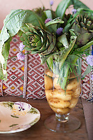 This very unusual flower arrangement features new potatoes in the bottom of the vase and fresh artichokes arranged with sprigs of flowering chives