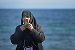 Rabia Fijay is a Syrian refugee from Aleppo, and here she uses a mobile phone to let her family know she has arrived safely on the Greek island of Lesbos on October 30, 2015. She was on a boat full of refugees that traveled to Lesbos from Turkey. The boat was provided by Turkish traffickers to whom the refugees paid huge sums to arrive in Greece.