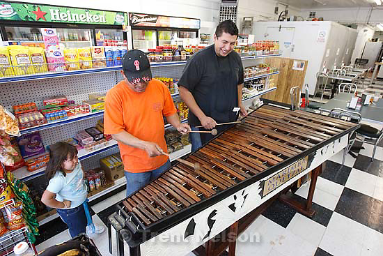 Magna - Jaime Perata, his daughter Maria Fernanda, and Daniel Argueta playing a large wooden Guatemalan marimba in the The Quetzal Market Wednesday, August 19 2009. The market opened up about 8 months ago and specializes in Central American foods.