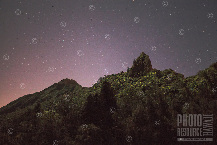 Mountain peak and range under a starry night sky near the Pali Lookout, O'ahu.