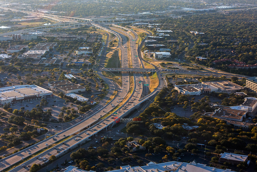 A morning aerial helicopter view during rush-hour of Highway 183 and Loop 360 Capital of Texas Highway overpass intersection north Austin, Texas. Mopac Expressway Loop 1 is seen in the far distance.