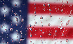 A United States flag is reflected in raindrops on a windshield. Jim Bryant Photo