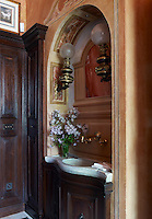 A stone wash basin in the bathroom is inset into an alcove which has been hand-painted with a mural